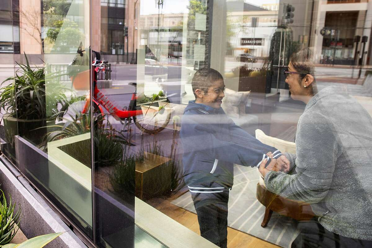 Olivia Fraga (right) and her ten-year-old son Martin Perez-Fraga at their apartment lobby on Tuesday, March 31, 2020, in San Francisco, Calif. With schools closed because of coronavirus pandemic, Martin is no longer receiving all the services he would get at school. Martin has Down syndrome.
