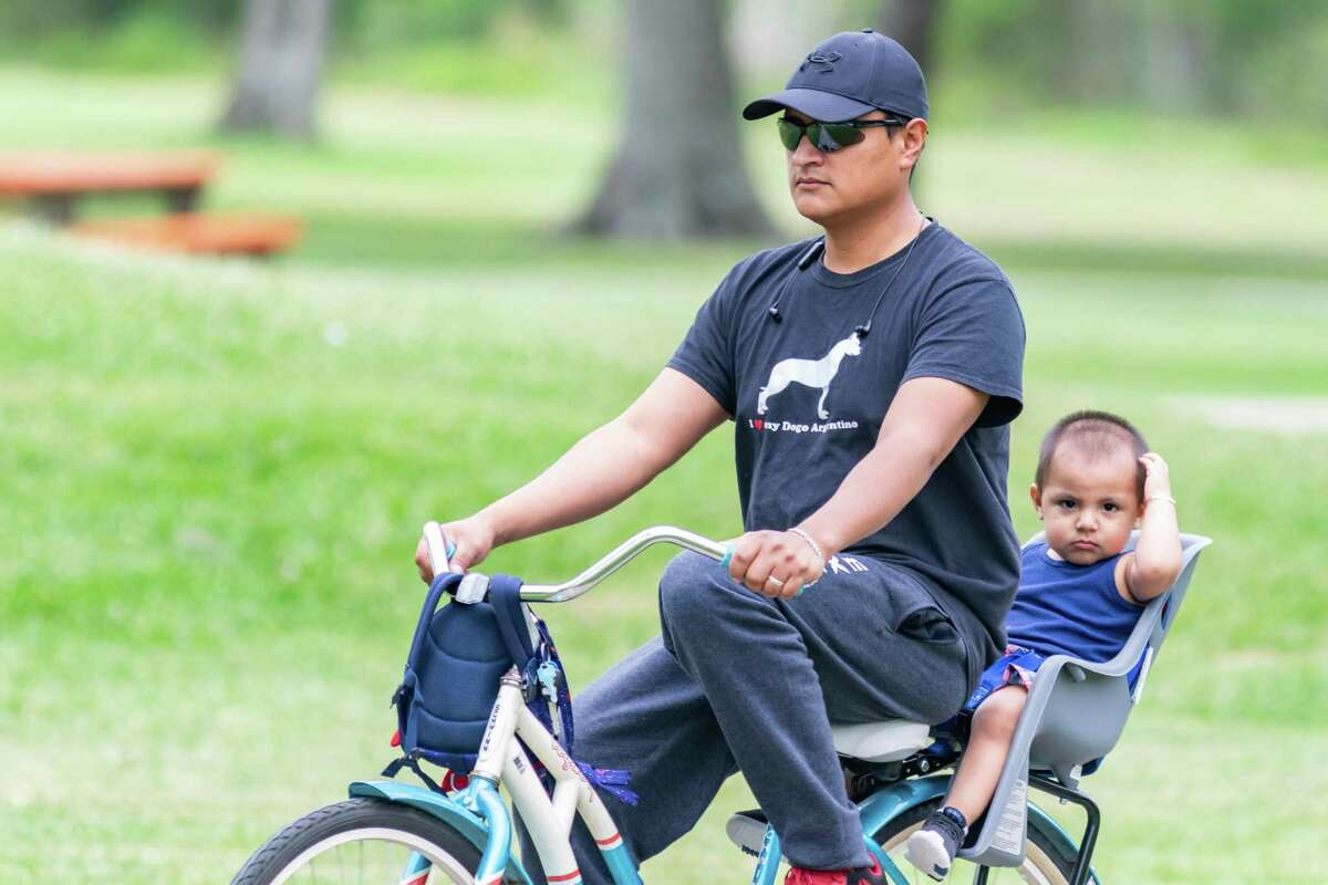 One-and-a half-year old Aiden gets a ride through Rogers Park with Luis Rivera on Saturday morning. Some folks were out in the park but were abiding by the latest coronavirus guidelines. Photo made on March 28, 2020. Fran Ruchalski/The Enterprise