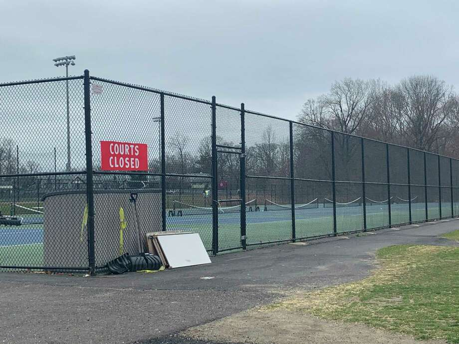 "The tennis courts at New Canaan High School, which were filled around 2:30 p.m. Friday, March 27, are empty and locked behind a ""Courts Closed"" sign around the same time Monday, March 30. New Canaan closed all town and school parks and fields to stop gatherings in an effort to slow the spread of the novel Coronavirus. Photo: John Kovach / Hearst Connecticut Media / New Canaan Advertiser"