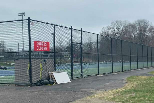 "The tennis courts at New Canaan High School, which were filled around 2:30 p.m. Friday, March 27, are empty and locked behind a ""Courts Closed"" sign around the same time Monday, March 30. New Canaan closed all town and school parks and fields to stop gatherings in an effort to slow the spread of the novel Coronavirus."