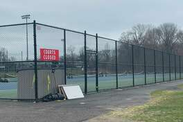 """The tennis courts at New Canaan High School, which were filled around 2:30 p.m. Friday, March 27, are empty and locked behind a """"Courts Closed"""" sign around the same time Monday, March 30. New Canaan closed all town and school parks and fields to stop gatherings in an effort to slow the spread of the novel Coronavirus."""