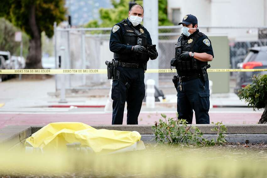 BART police officers investigate the case of a deceased male outside Lake Merritt Station in March. The board has proposed de-emphasizing police this fall.