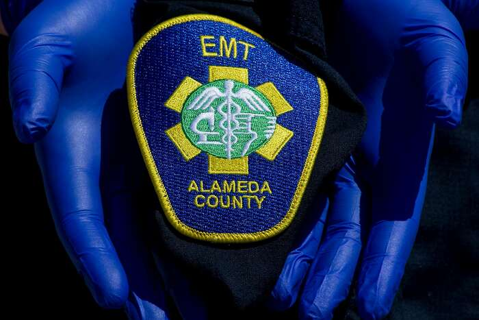An Alameda County EMT wears gloves while holding their EMT patch on their work shirt while posing for a portrait at an undisclosed location in the Bay Area, Calif. Thursday, April 2, 2020. Alameda County EMTs and paramedics have been sidelined because of sickness or exposure to COVID-19. Many are not offered any additional paid time off and in many cases haven't accrued enough of their own vacation or sick days to be paid.