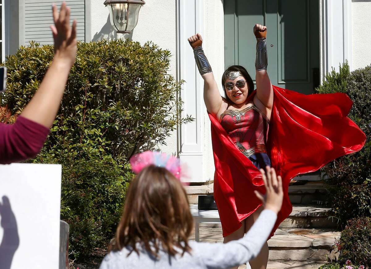 Serenity Pang and her family dressed as super heroes to celebrate Aria Groff (foreground) on her sixth birthday in Alameda, Calif. on Wednesday, April 1, 2020. Aria and her family drove to the homes of 16 of her friends with each wishing a happy birthday and providing the clue for their next stop on the drive-by birthday scavenger hunt.