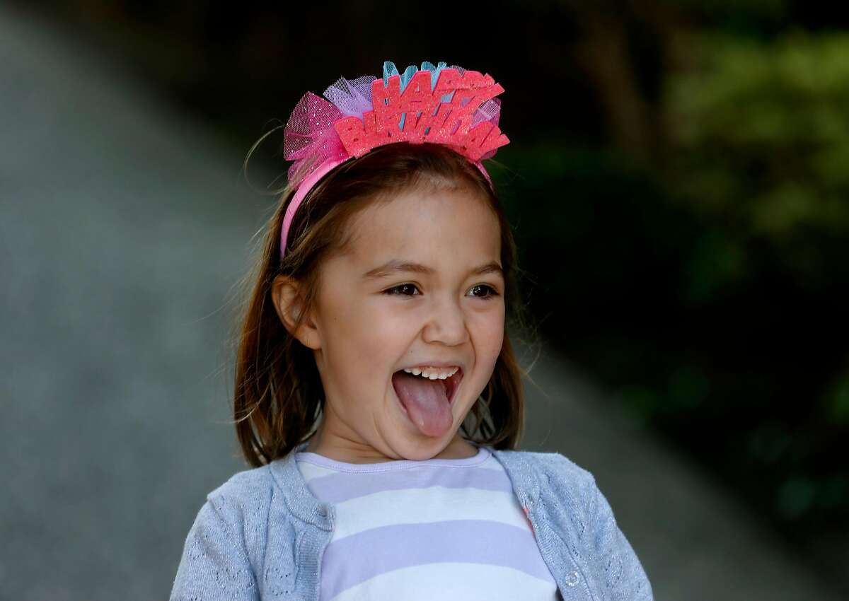 Aria Groff enjoys a mobile scavenger hunt to celebrate her sixth birthday in Alameda, Calif. on Wednesday, April 1, 2020. Aria and her family drove to the homes of 16 of her friends with each wishing a happy birthday and providing the clue for their next stop on the hunt.