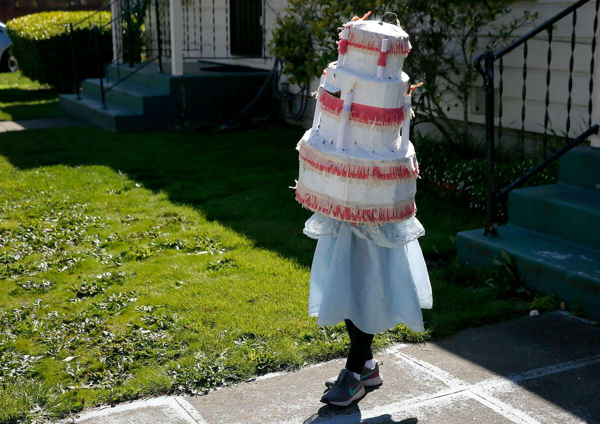 Ruby Weglarz, 6, wears a birthday cake pi-ata to celebrate her friend Aria Groff's sixth birthday at a stop for a drive-by scavenger hunt in Alameda, Calif. on Wednesday, April 1, 2020. Aria and her family drove to the homes of 16 of her friends with each wishing a happy birthday and providing the clue for their next stop on the hunt.