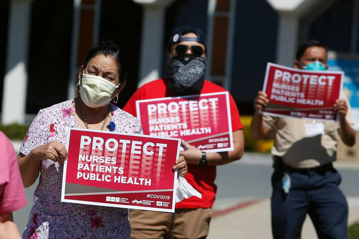 Adela Melara (left), Seton Medical Center environmental worker, rallys with nurses, staff members and supporters against the lack of personal protective equipment and other protections for frontline health care workers during the coronavirus pandemic at Seton Medical Center on Thursday, April 2, 2020 in Daly City, CA.