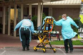 Emergency medical services personnel respond to a call at Southeast Nursing and Rehabilitation Center in San Antonio on April 2, 2020. An outbreak of COVID-19 has killed one resident. Another 66 of 84 residents are infected. Some employees have also tested positive.
