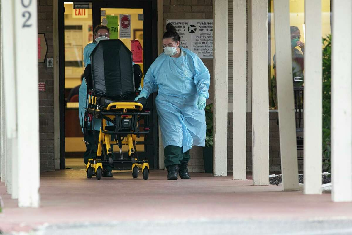 Emergency medical services personnel leave with an empty stretcher after responding to a call at Southeast Nursing and Rehabilitation Center in San Antonio on April 2, 2020. An outbreak of COVID-19 has killed one resident. Another 66 residents are infected. Some employees have also tested positive.