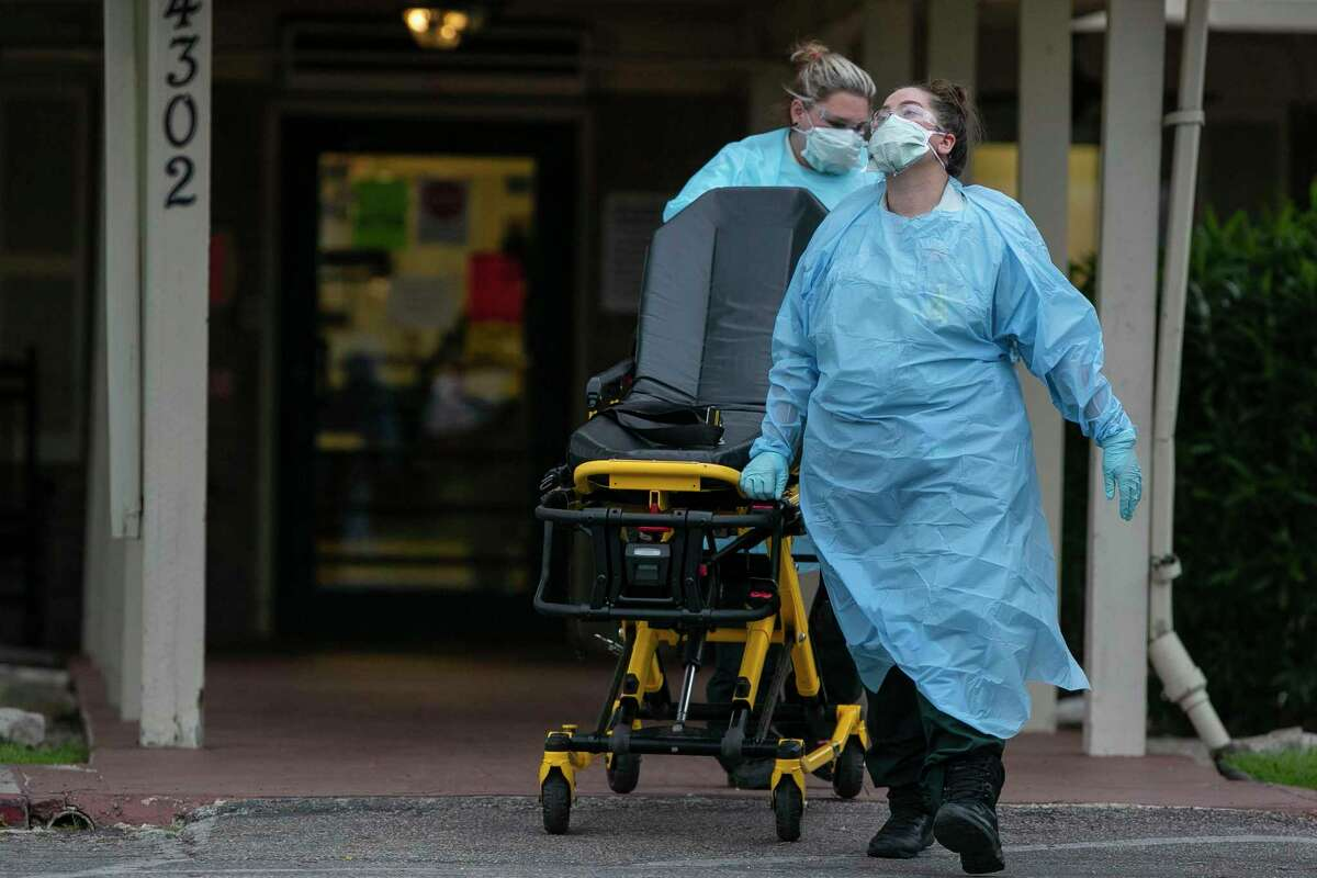 EMS personnel leave with an empty stretcher after responding to a call at Southeast Nursing & Rehabilitation Center in San Antonio, Texas, April 2, 2020. It was announced Wednesday that an outbreak of COVID-19 has killed one resident and infected at least 14 others.