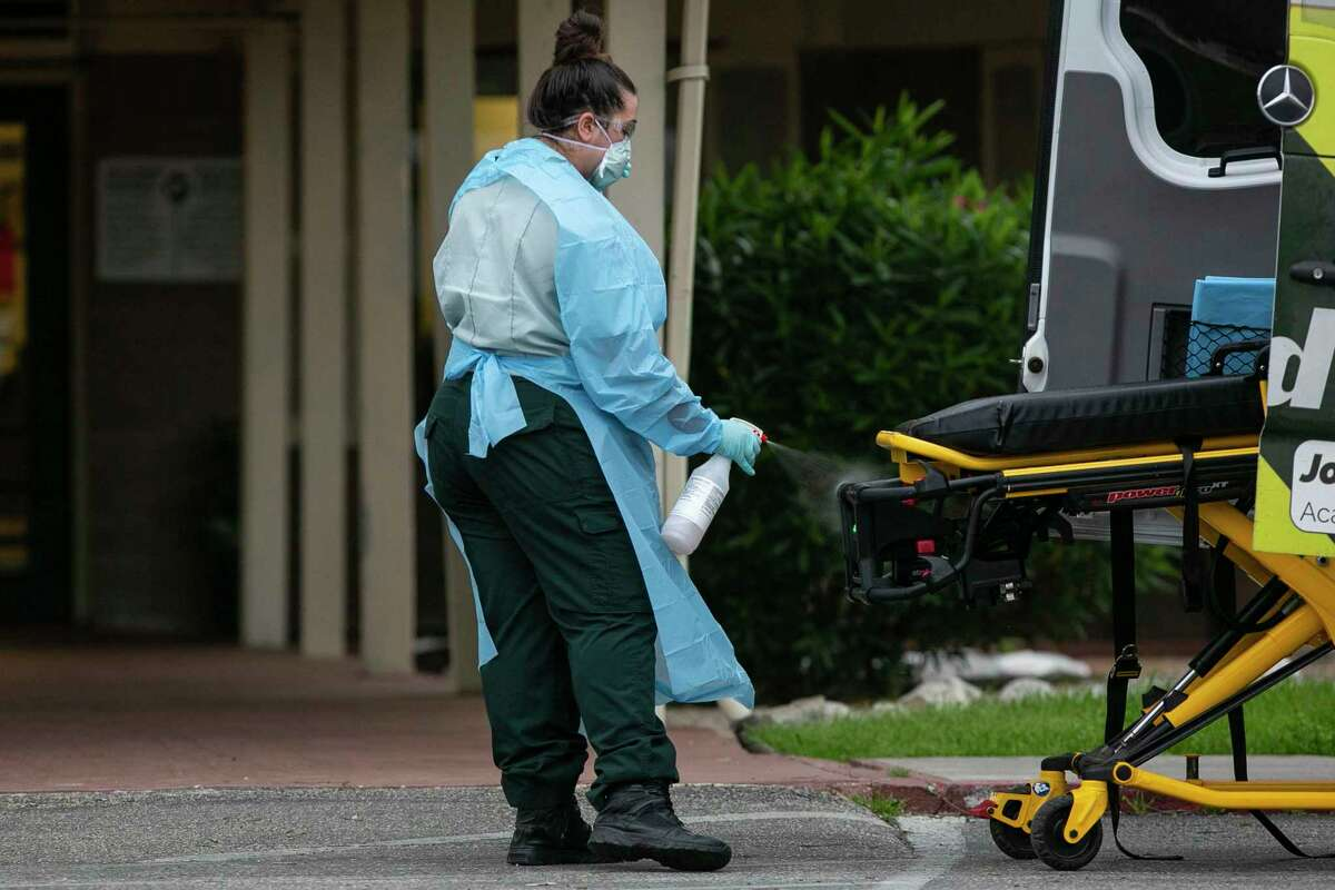 An EMS personnel member disinfects a transport stretcher after responding to a call at Southeast Nursing & Rehabilitation Center in San Antonio, Texas, April 2, 2020. It was announced Wednesday that an outbreak of COVID-19 has killed one resident and infected at least 14 others.