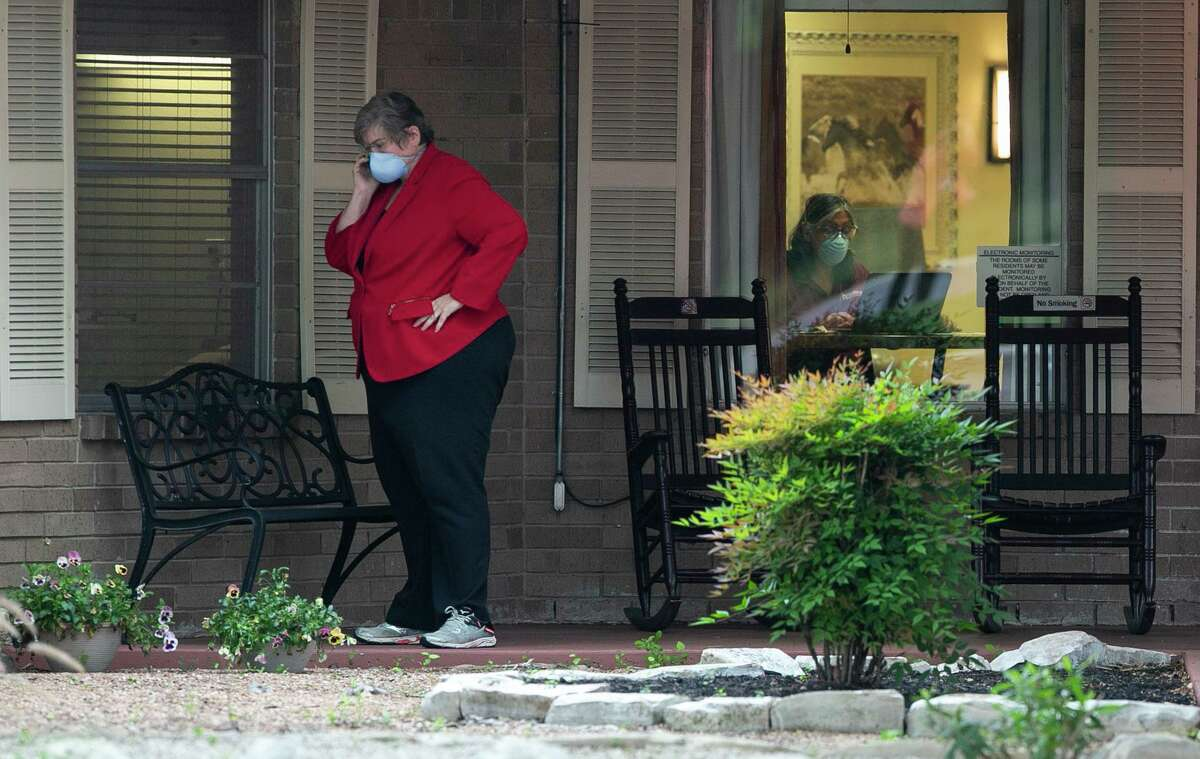 A facility personal member takes a phone call wearing a mask outside the Southeast Nursing & Rehabilitation Center in San Antonio, Texas, April 2, 2020.