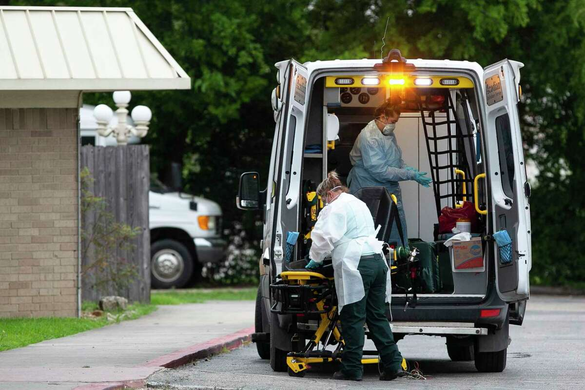 EMS personnel members disinfect equipment after responding to a call at Southeast Nursing & Rehabilitation Center in San Antonio, Texas, April 2, 2020.