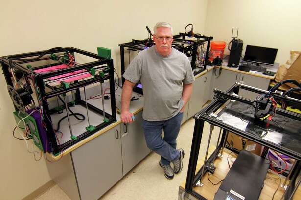 Charlie Conway, Executive Director at AccessIndependence, poses in front of several 3D printers at the company in Stratford, Conn., on Thursday Mar. 2, 2020. With materials on hand Conway is working to make 2,000 masks for medical personnel with a goal of making 10,000.