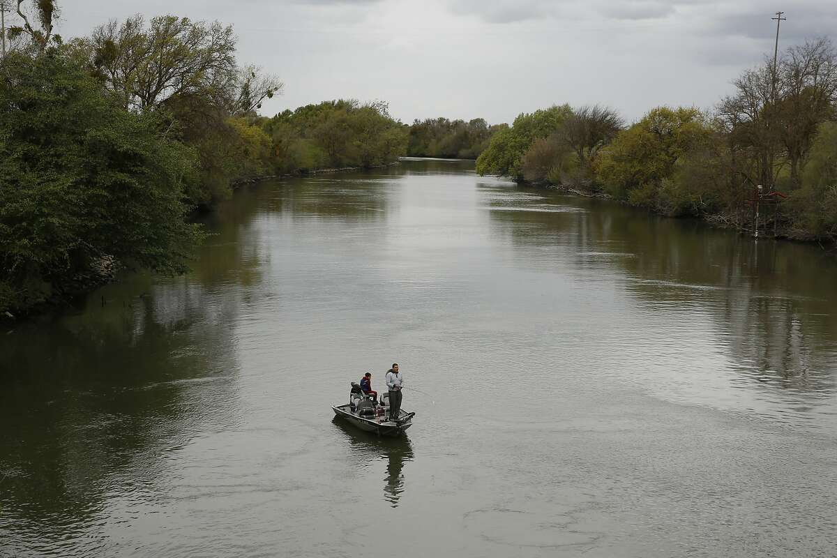 In this photo taken Tuesday, March 24, 2020, people fish in the Sacramento-San Joaquin River Delta's Elk Slough near Courtland, Calif. California regulators on Tuesday, March 31, 2020, announced a set of new rules on how much water can be taken from the state's largest rivers that run through the delta. The new rules have angered water agencies for limiting how much they can take. But the rules have also angered environmental groups, who say the limits are not low enough to protect endangered species. (AP Photo/Rich Pedroncelli)