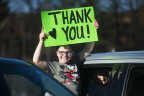 Midland residents gather in a parking lot outside of MidMichigan Medical Center-Midland to show their appreciation for healthcare workers by holding signs, cheering and honking their horns Thursday, April 2, 2020. (Katy Kildee/kkildee@mdn.net)