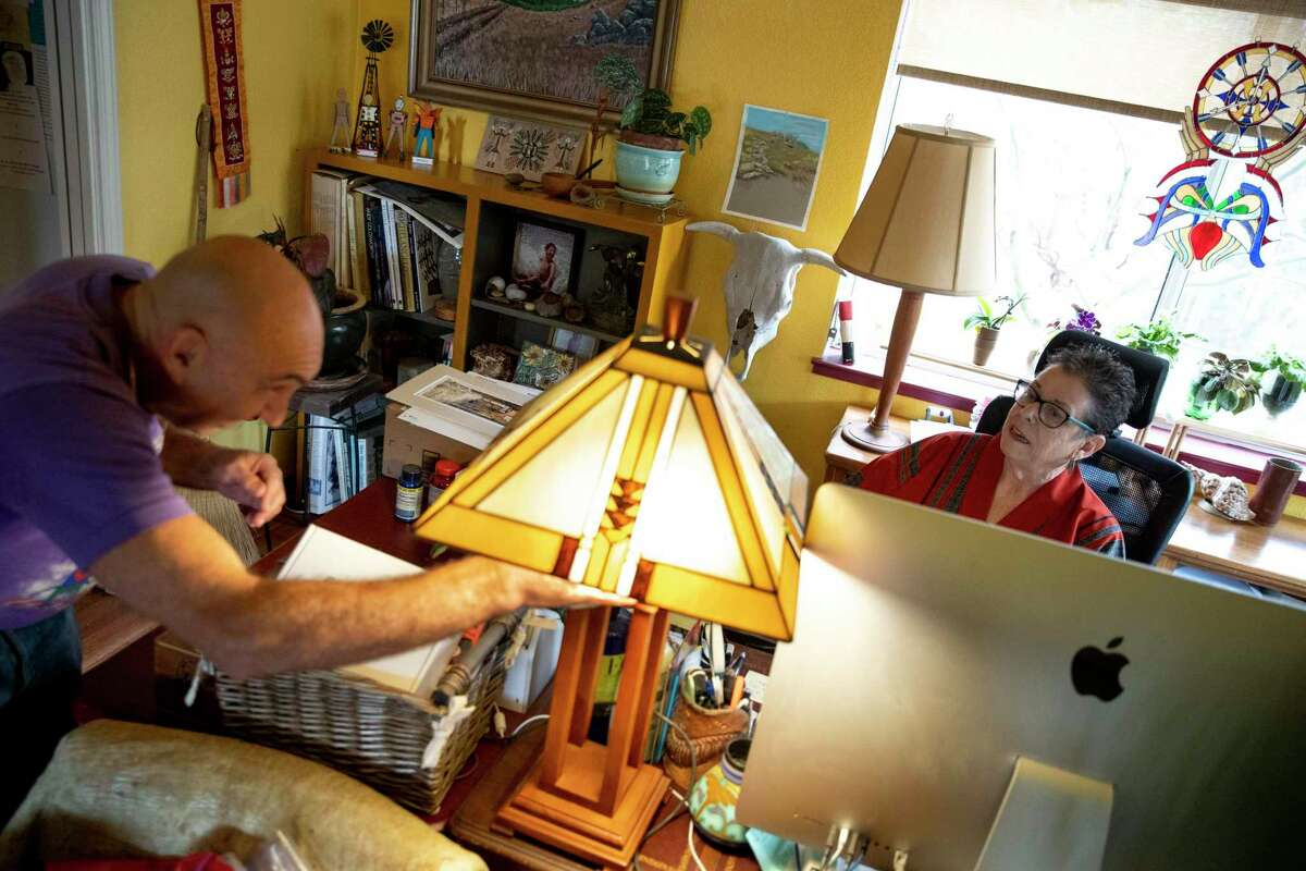 David Stahlberg, left, wipes down his home as Donnee Komisar uses her computer at home. Komisar's doctor advised her to wear a mask, but she said she wasn't able to get one.