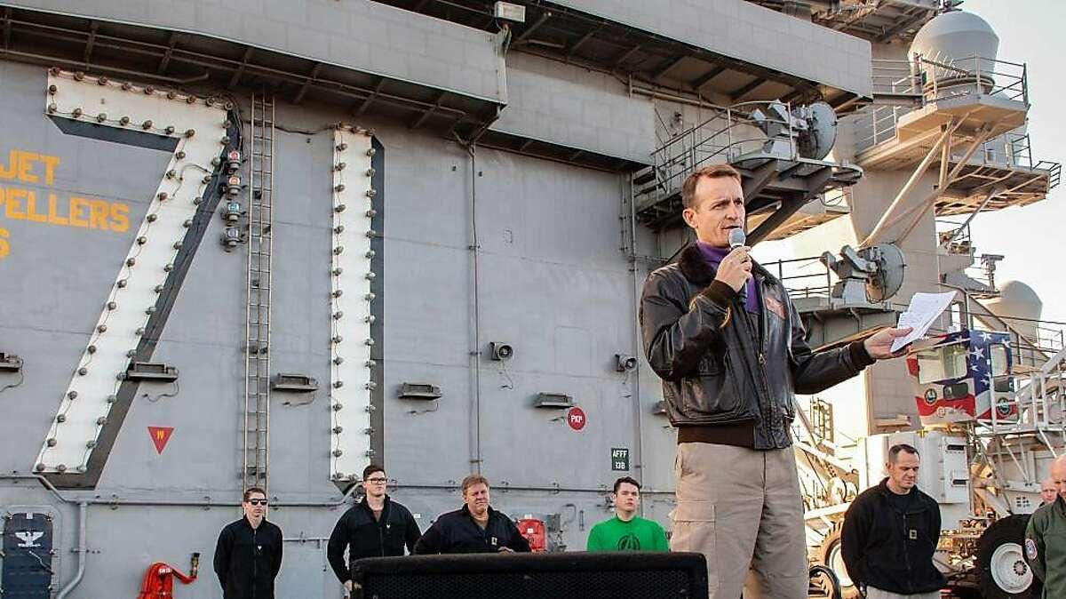 Capt. Brett Crozier, commanding officer of the aircraft carrier USS Theodore Roosevelt (CVN 71), gives remarks during an all-hands call on the ship's flight deck Dec. 15, 2019. (Seaman Alexander Williams/ U.S. Navy)