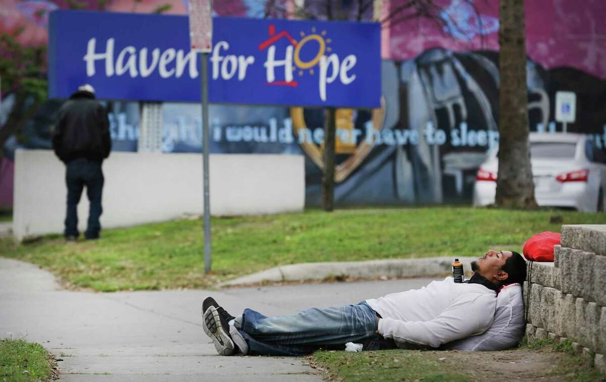 A homeless man sleeps on the sidewalk Thursday next to Haven for Hope, which has stopped taking in new people looking for shelter.