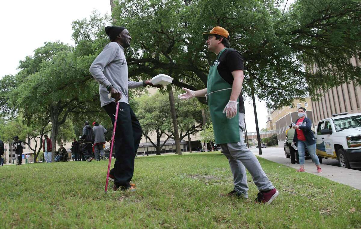 Pastor Gavin Rogers (right) hands a meal to a man at Madison Square Park on Thursday. Rogers and Chef John Chadwell of Corazon Ministries at Travis Park Church helped prepare and provide meals. Before the restrictions placed to slow the coronavirus spread, the meals would be provided at the church. Regulars already know the drill and practice social distancing.