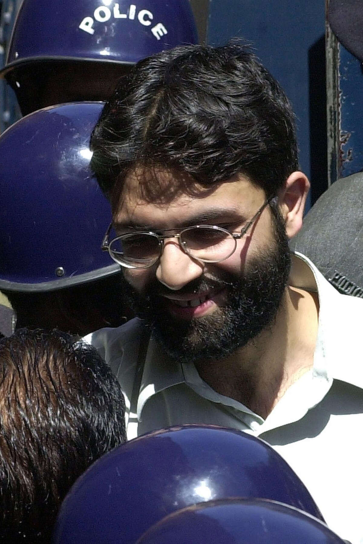 (FILES) In this file taken on March 29, 2002, Sheikh Omar, chief suspect of slain US journalist Daniel Pearl smiles while talking to Pakistani police officials in Karachi. - A Pakistani court on April 2, 2020 overturned the death sentence for British-born militant Ahmed Omar Saeed Sheikh, who had been convicted over the 2002 killing of American journalist Daniel Pearl. (Photo by Aamir QURESHI / AFP) (Photo by AAMIR QURESHI/AFP via Getty Images)