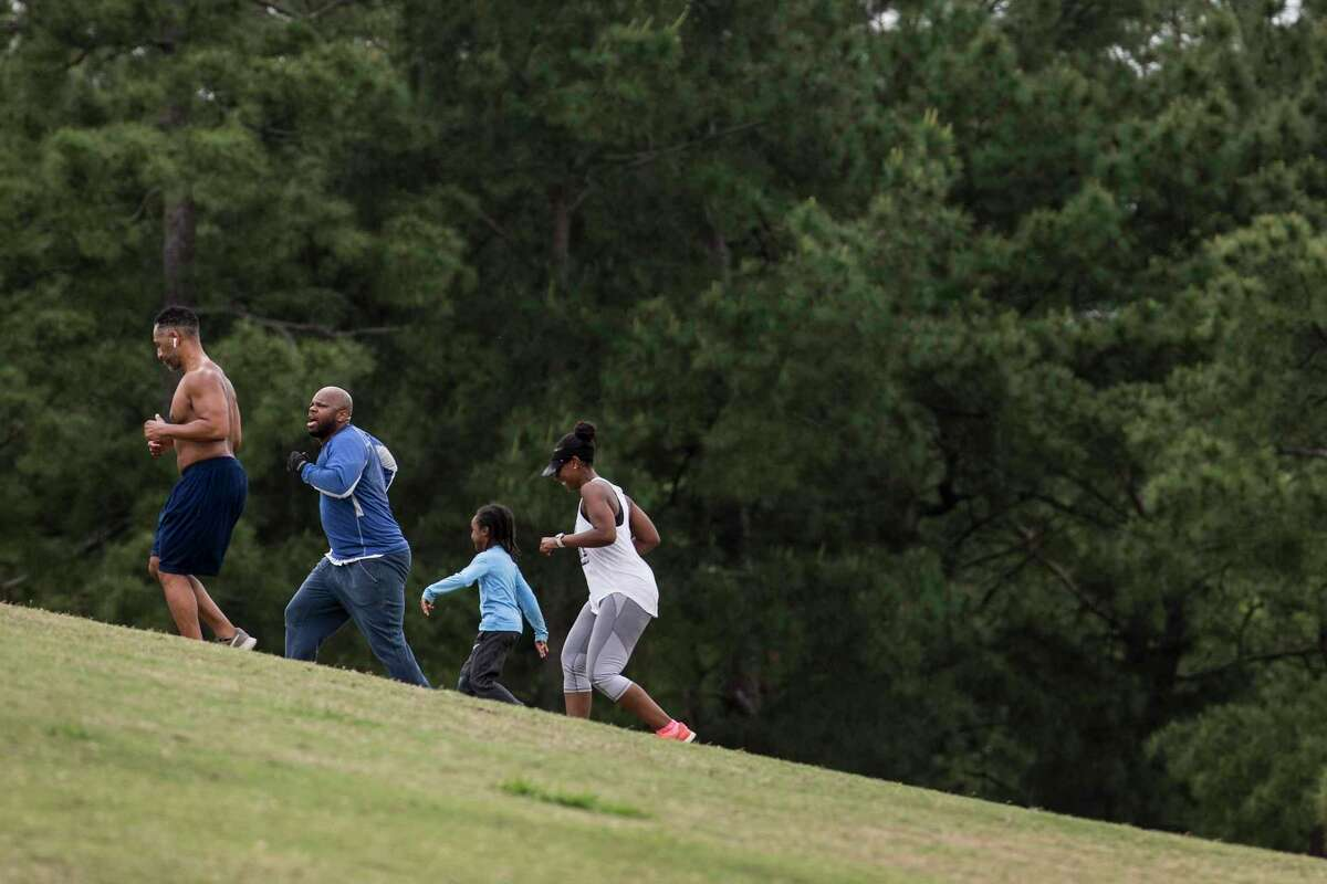 Texas residents who want to exercise outdoors, such as these seen running in Hermann Park on Thursday, will still be able to do so under Gov. Greg Abbott's statewide stay-at-home order.