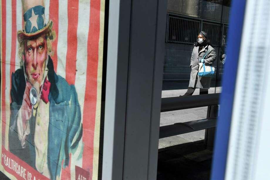 A pedestrian wears a mask in Washington on Thursday, April 2, 2020. Photo: Washington Post Photo By Matt McClain / The Washington Post