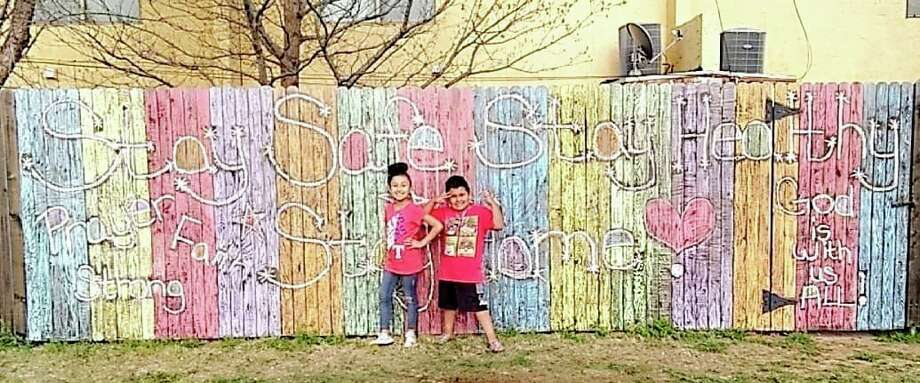 Jabree Garcia, 7, and 5-year-old Jordan Garcia, stand in front of a message of hope painted on a fence at their house. Photo: Courtesy Photo/Bre Flores