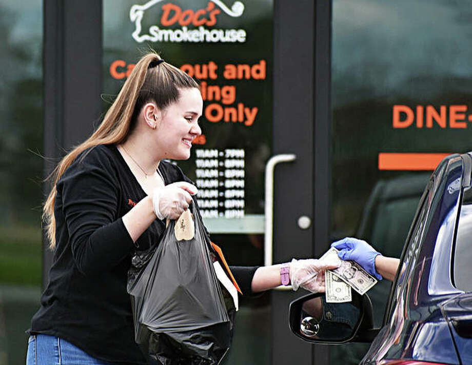 A Doc's Smokehouse employee hands off a bag of food to a customer via curbside pickup Tuesday afternoon in Edwardsville. Photo: Matt Kamp | The Intelligencer