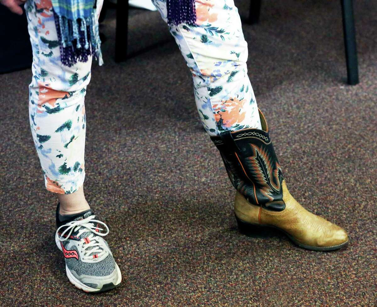"""Alpha Home staff member Melissa Dobbertin wears mismatching foot apparel at the nonprofit's recent Spirit Day. Like many substance abuse treatment programs in Bexar County, staff and clients have had to adjust to a """"new normal"""" because of the coronavirus."""
