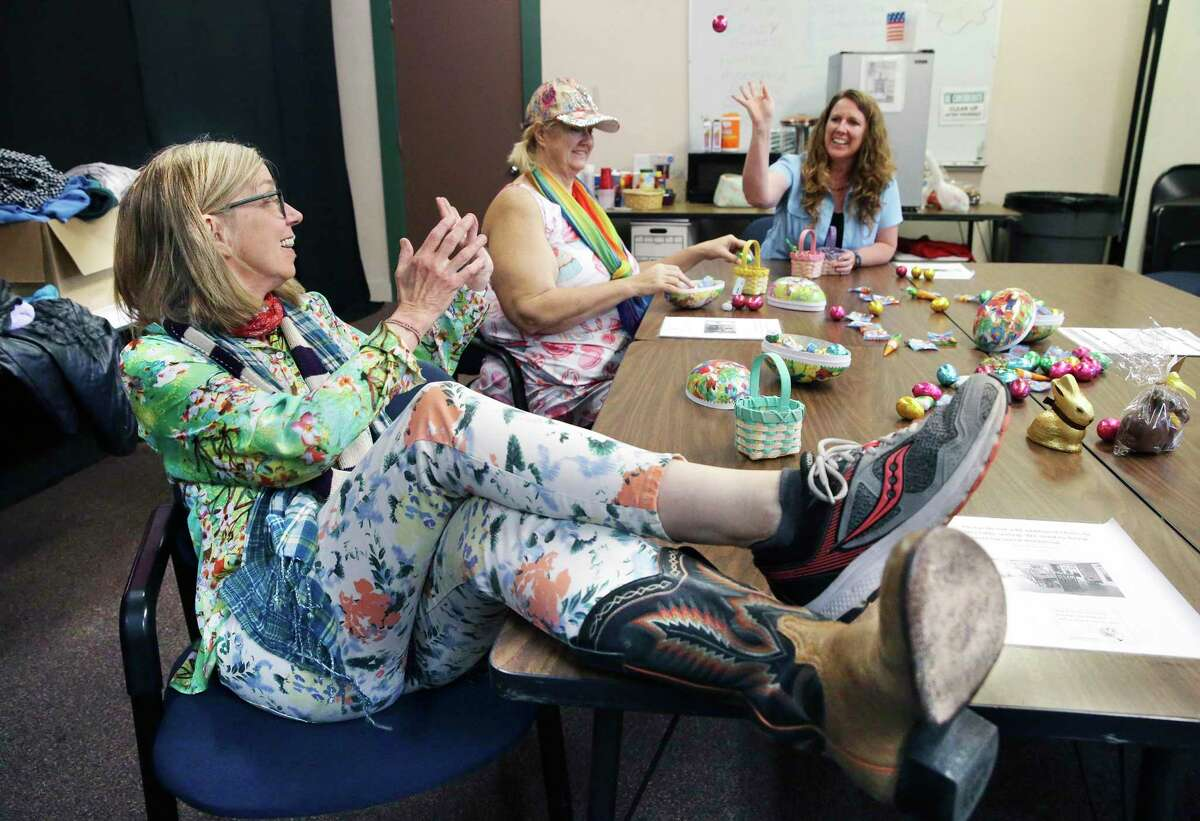 Alpha Home CEO Merideth Erickson passes chocolate eggs to staff members Viki Lynn Trautman and Melissa Dobbertin as they stuff Easter baskets for staff. Erickson said her nonprofit has experienced some declining enrollments because of the virus.