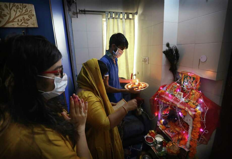 FILE - In this Wednesday, March 25, 2020 file photo, a family, wearing face masks as a precaution from the COVID-19 coronavirus, prays inside their home in New Delhi to mark the start of the Navratri festival, where Hindus fast for nine days. The world's largest democracy went under the world's biggest lockdown Wednesday, with India's 1.3 billion people ordered to stay home in a bid to stop the pandemic from spreading and overwhelming its health care system. (AP Photo/Manish Swarup) / Copyright 2020 The Associated Press. All rights reserved.