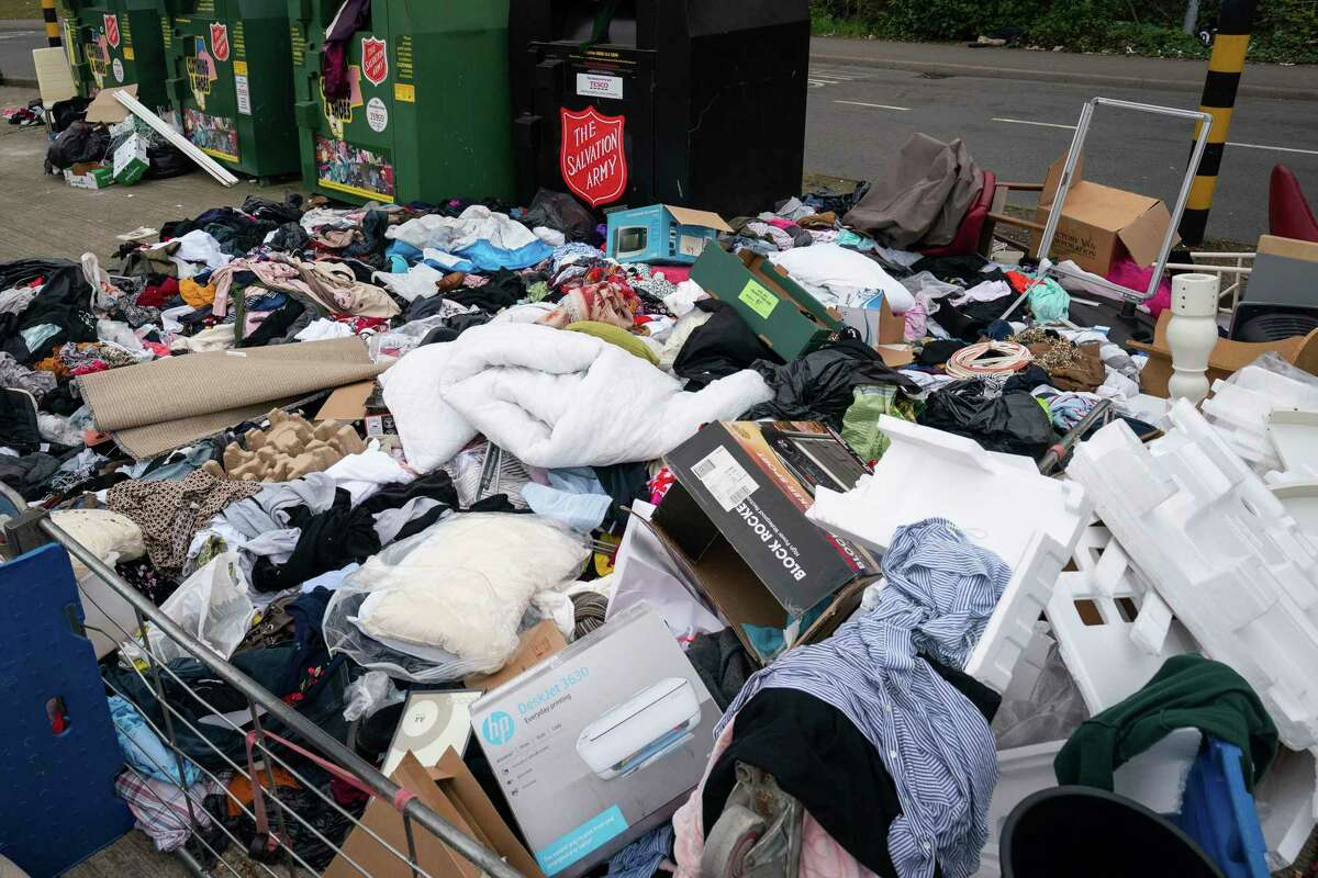 Rubbish stacked high by a recycling point at Tesco Extra in Wembley, England, Friday April 3, 2020, due to the recycling centres being closed amid the growing coronavirus outbreak. (Aaron Chown/ PA via AP)