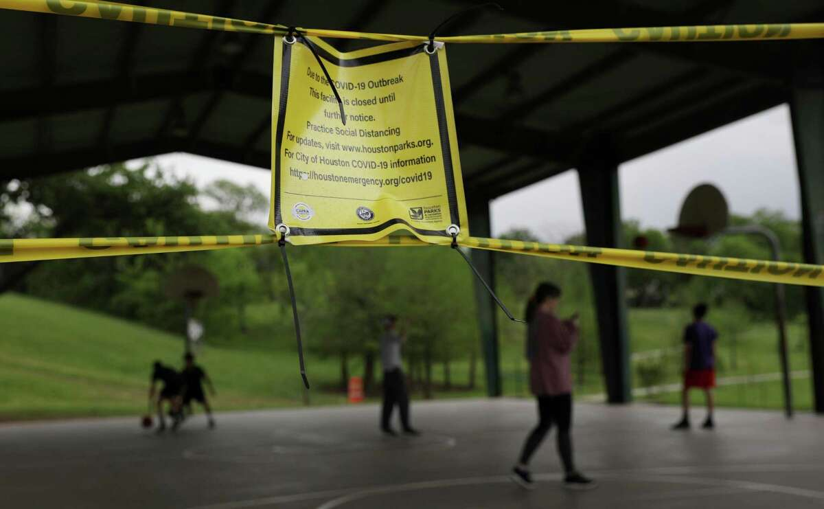People play basketball as a sign indicates that the court is closed due to concerns about COVID-19 on Saturday, March 28, 2020, at Spotts Park in Houston.