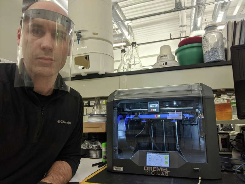 SUNY Poly nanobioscience professor Nate Cady making face mask shields with a 3-D printer at the school's Albany campus.
