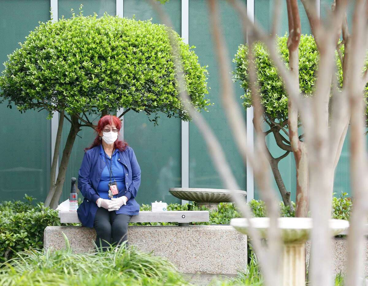 An employee of the San José Clinic in the Midtown neighborhood in Houston waits outside to screen people who enter the clinic on Thursday, April 2, 2020.