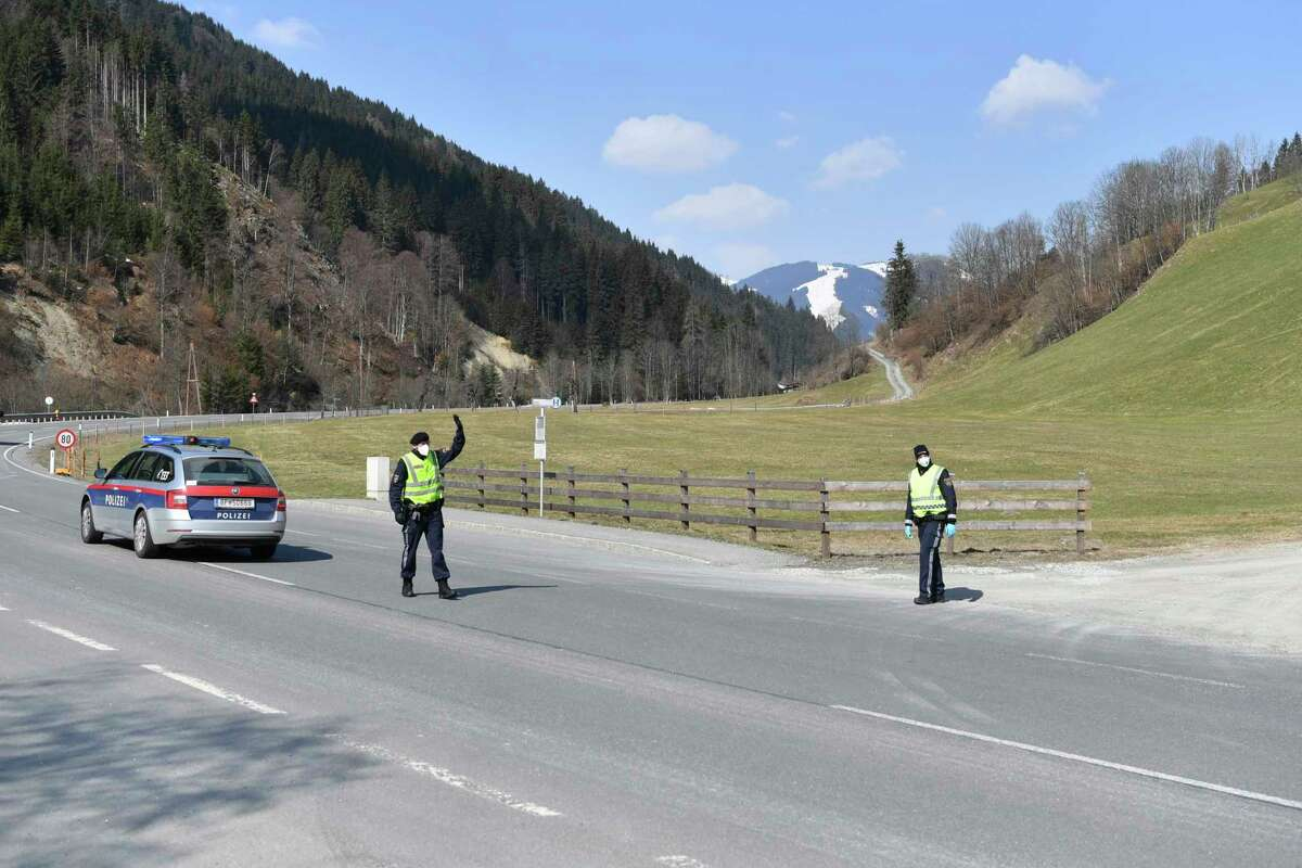 Police officers block the road to the skiing resort Saalbach Hinterglemm, Austrian province of Salzburg, Friday, April 3, 2020 after the city was quarantined.
