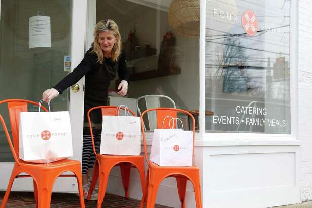 Megan Ruppenstein, co-owner of Four Forks, puts out some bags for pick-up.