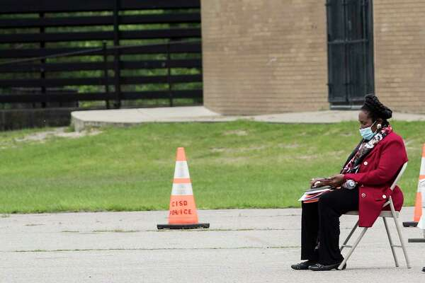 Rep. Sheila Jackson Lee, D-Texas, sits alone in the parking lot at Forest Brook Middle School working on her phone at a free coronavirus testing site on Thursday, April 2, 2020 in Houston.