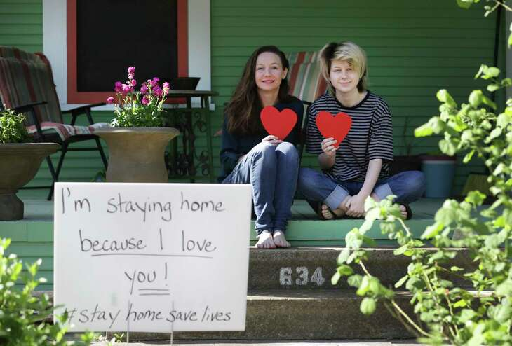 Christina Wright, left, President of the Alta Vista Neighborhood Association, and her daughter Neveah Crump, 15, have placed stuffed animals in a window and happy message signs in the yard.