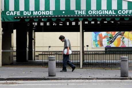 FILE - In this Friday, March 27, 2020 file photo, a man walks past the closed Cafe Du Monde restaurant in the French Quarter of New Orleans. It's normally bustling with tourists, but now nearly deserted due to the COVID-19 coronavirus pandemic. While rich in history and culture, New Orleans is economically poor, and many here are not necessarily well-positioned to weather this latest storm. (AP Photo/Gerald Herbert)