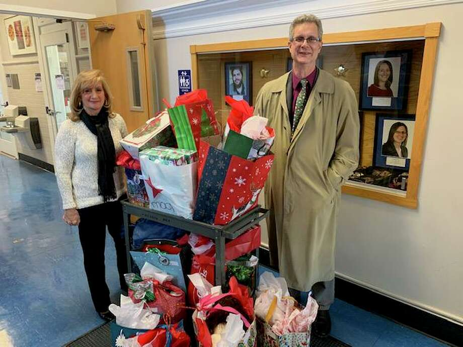 Operations Manager Angela Flynn and Associate Dean Michael J. Rossi of the College of Arts and Sciences at the University of New Haven flank a cart of gift bags recently. The UNH college partnered this year with city Youth and Family Services Director Robert S. Morton to adopt a West Haven family for the holidays. Under the leadership of Flynn and interim Dean Elizabeth Ann Beaulieu, the college collected toys, clothes, books and other donations from more than 20 people for a deserving family. Photo: Contributed Photo