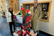 Operations Manager Angela Flynn and Associate Dean Michael J. Rossi of the College of Arts and Sciences at the University of New Haven flank a cart of gift bags recently. The UNH college partnered this year with city Youth and Family Services Director Robert S. Morton to adopt a West Haven family for the holidays. Under the leadership of Flynn and interim Dean Elizabeth Ann Beaulieu, the college collected toys, clothes, books and other donations from more than 20 people for a deserving family.
