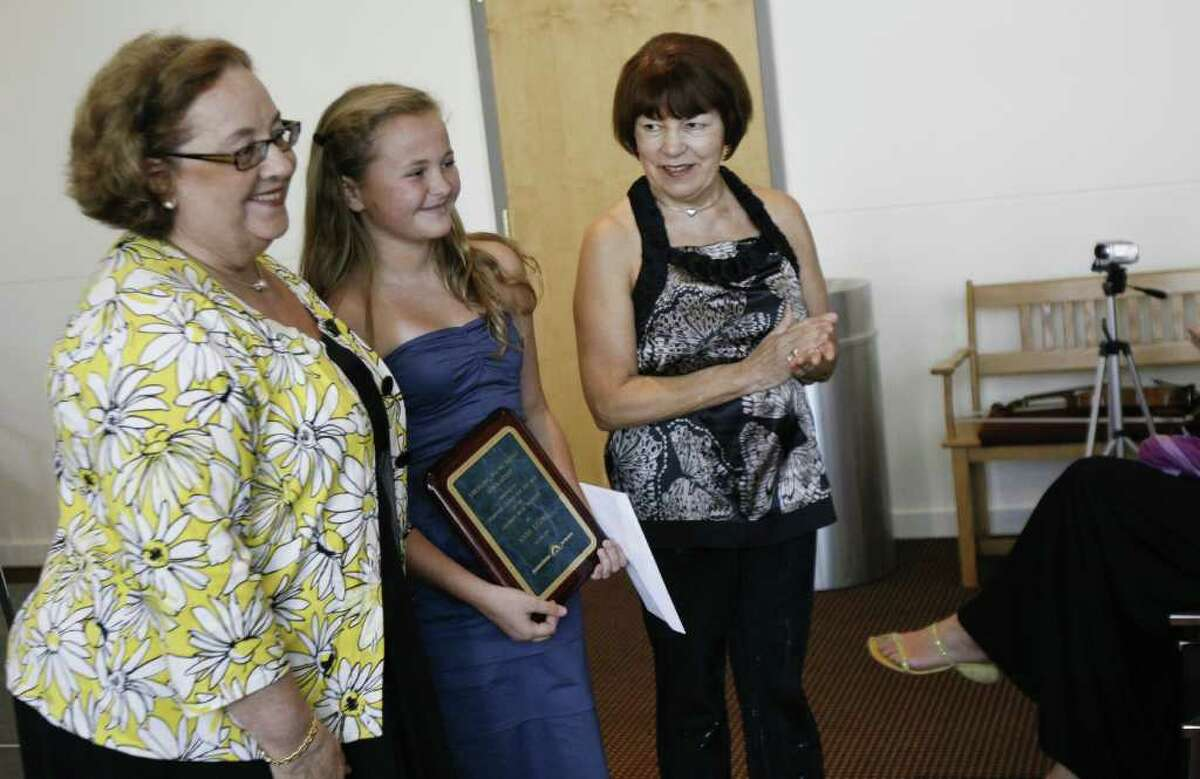Elissa Getto, left, executive director of the Stamford Center For the Arts, and Asya Meshberg, right, artist director of the Chamber Music Institute for Young Musicians, present a scholarship and plaque to Anna Leunis, center, age 14, on Sunday, August 8, 2010. The scholarship is given on behalf of the SCA to help students pursue their musical talents.