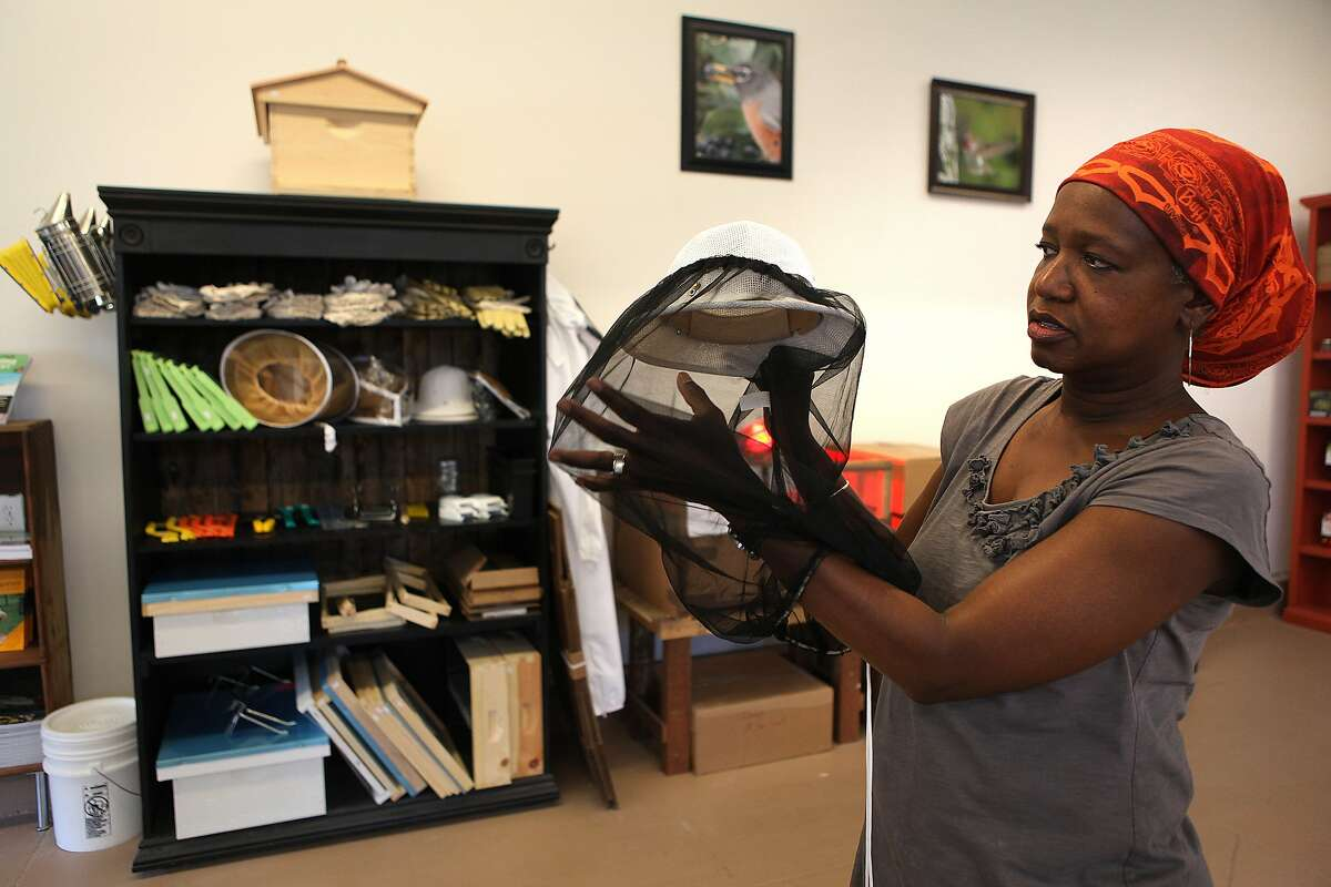Yolanda Burrell, owner of Pollinate in Oakland, shows a bee hat at her urban farm store in Oakland.