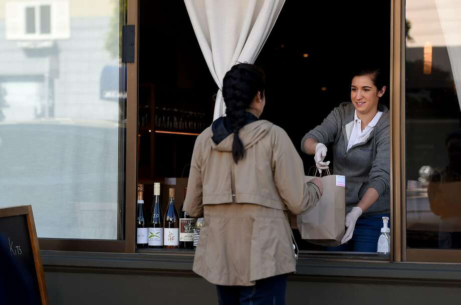 An employee for Atelier Crenn restaurant hands a takeout order to a customer through a window in San Francisco, California on April, 1, 2020, during the novel coronavirus outbreak. - The US death toll from the coronavirus pandemic topped 5,000 late on April 1, according to a running tally from Johns Hopkins University. (Photo by Josh Edelson / AFP) (Photo by JOSH EDELSON/AFP via Getty Images) Photo: Josh Edelson, AFP Via Getty Images