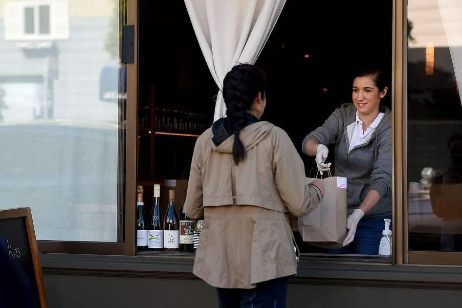 An employee for Atelier Crenn restaurant hands a takeout order to a customer through a window in San Francisco, California on April, 1, 2020, during the novel coronavirus outbreak. - The US death toll from the coronavirus pandemic topped 5,000 late on April 1, according to a running tally from Johns Hopkins University. (Photo by Josh Edelson / AFP) (Photo by JOSH EDELSON/AFP via Getty Images)