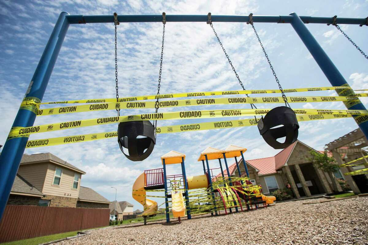 A playground is covered on caution tape, to discourage people from playing there due to coronavirus, in the Legends Trace subdivision on Sunday, March 29, 2020 in Spring.