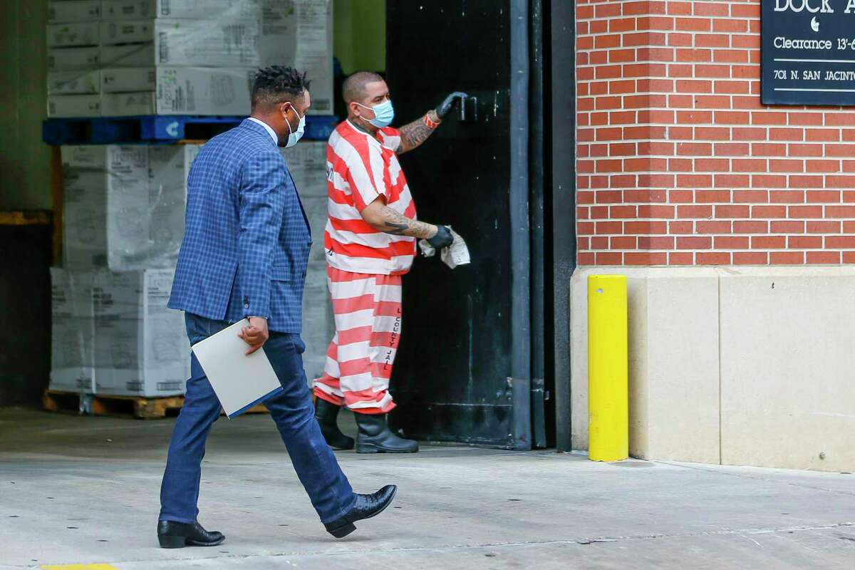 Harris County Jail inmates wear masks as they clean a loading dock, Friday, April 3, 2020, at the Harris County Jail in downtown Houston.