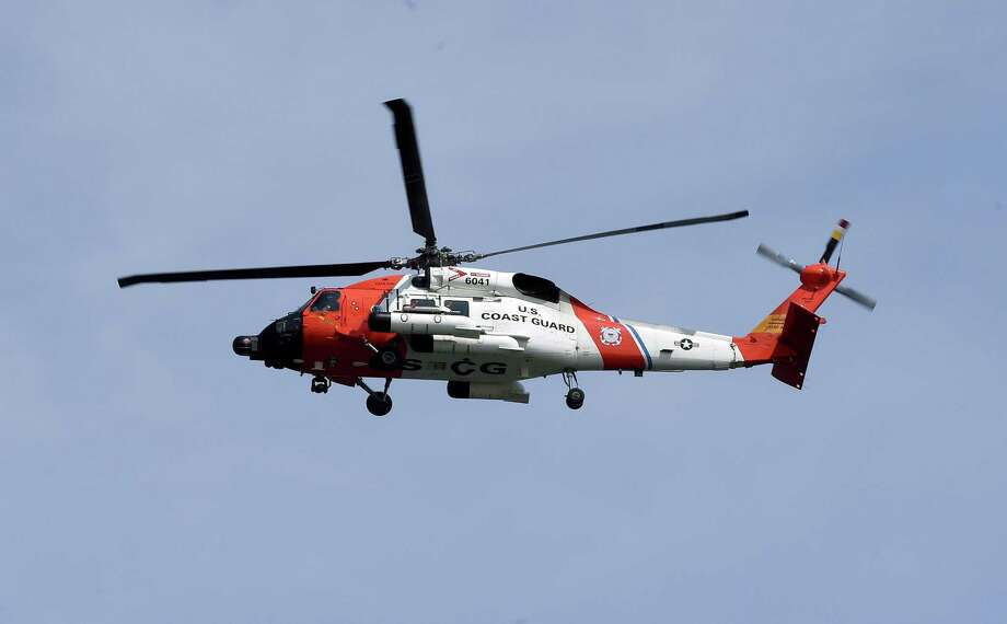 FILE - A Coast Guard helicopter in Milford, Conn. on 7/21/2017. A crewmember of a container ship off the coast of California was airlifted to a hospital after becoming injured on the ship.